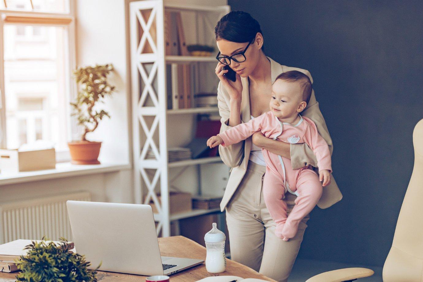Mãe empreendedora segura bebê enquanto fala ao telefone e usa o computador: trabalho de casa, home office
