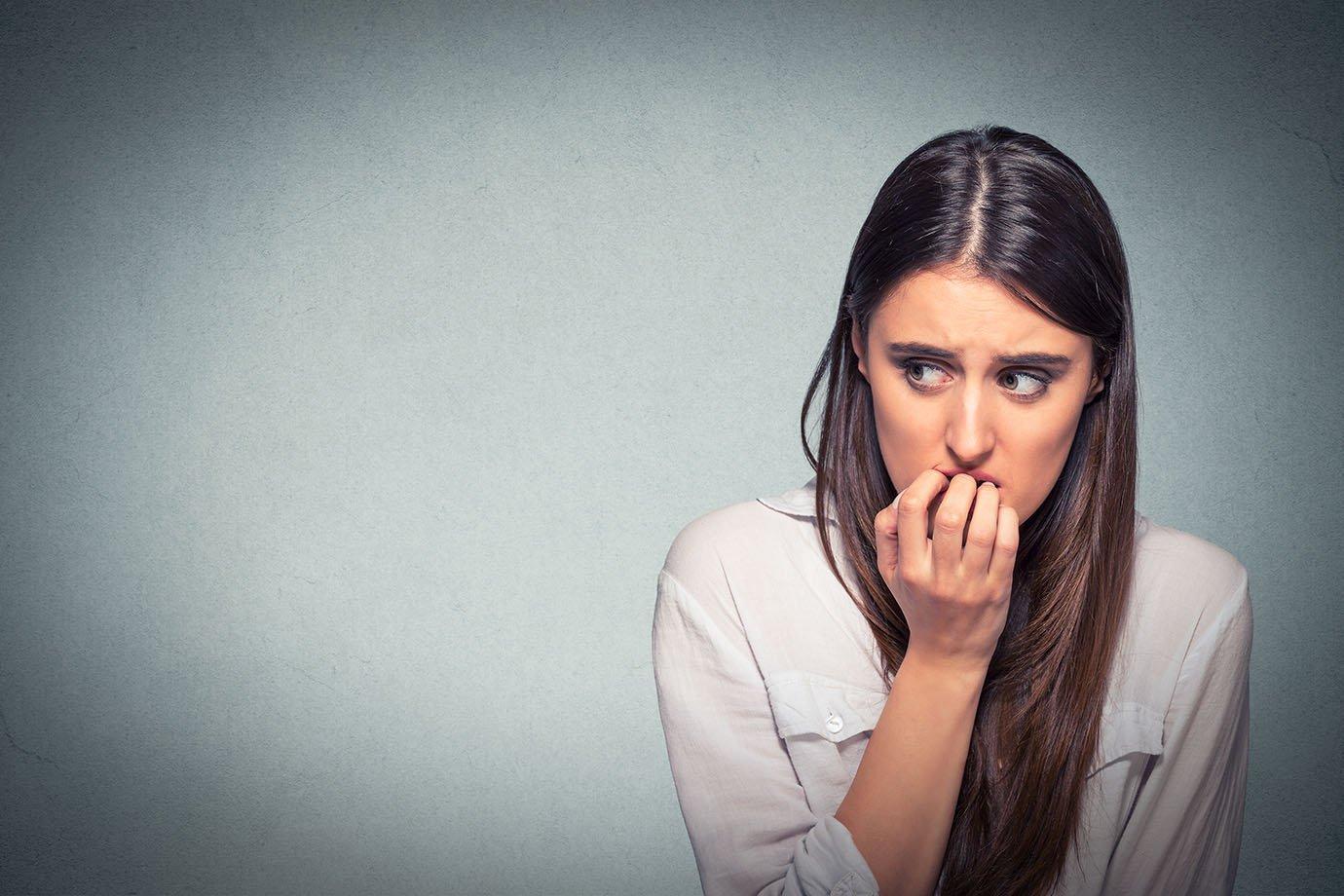 Mulher nervosa, com ansiedade, roendo as unhas, estressada