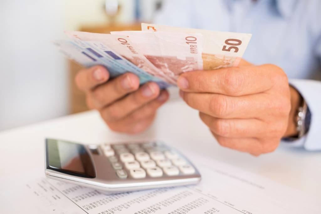 Homem com calculadora e dinheiro