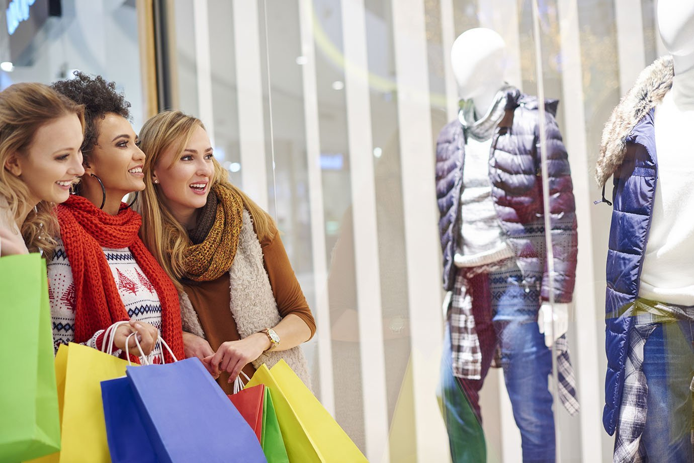 Mulheres olham para vitrine de loja de roupas, com sacolas