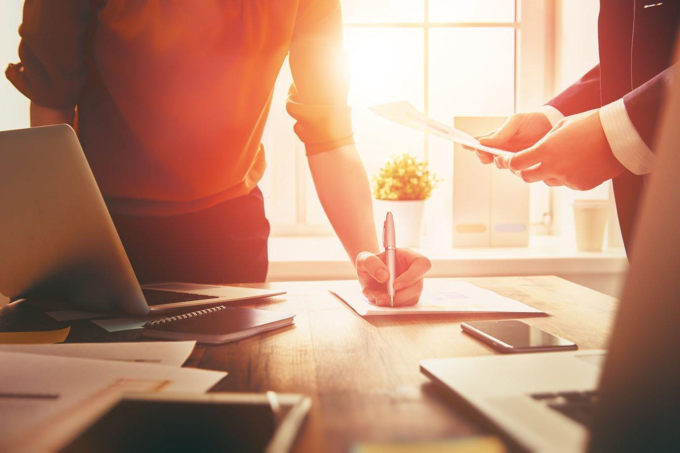 Homem e mulher em mesa de trabalho, escrevendo: reunião, ideias, planejamento