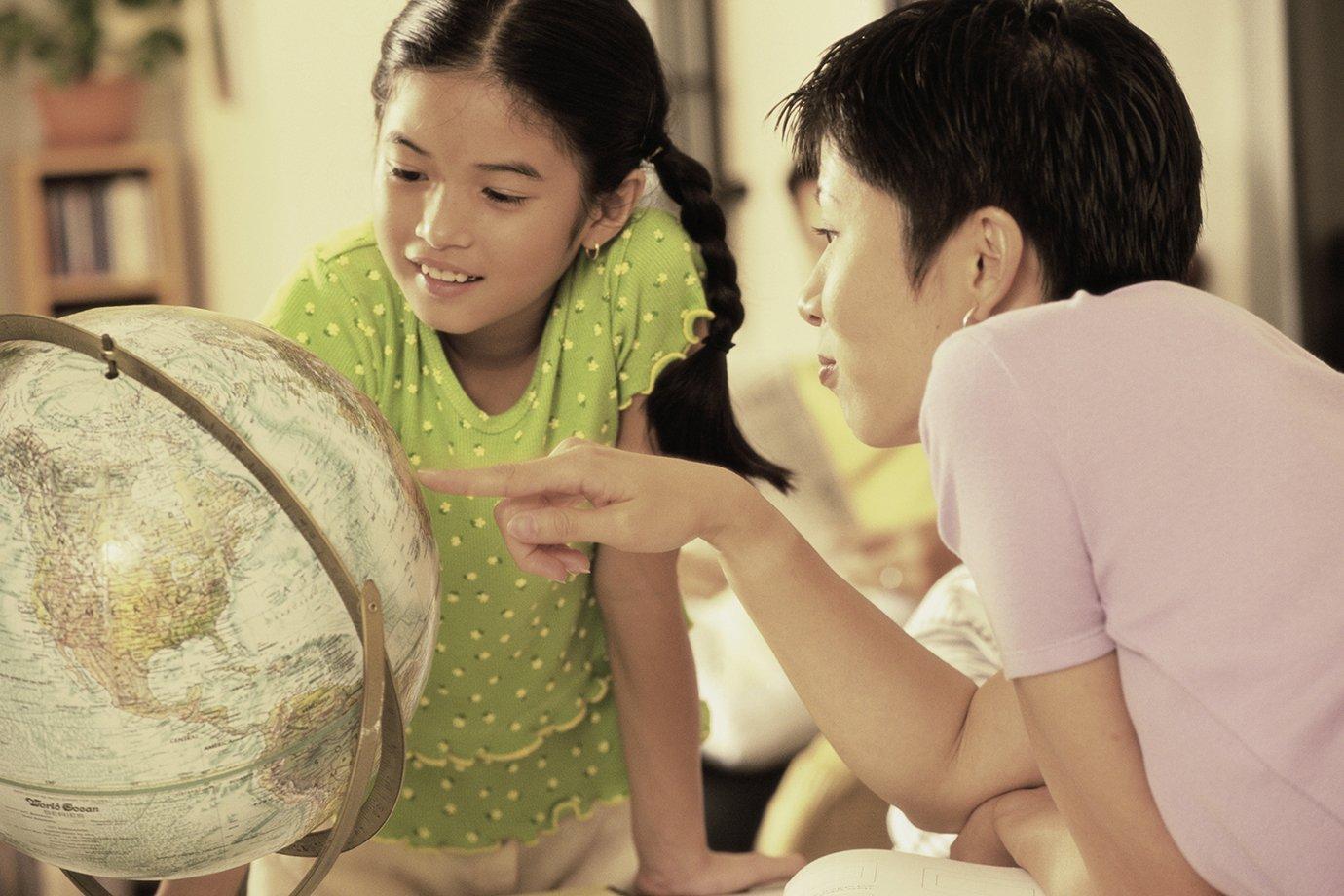 Mulher aponta para globo e ensina geografia a criança