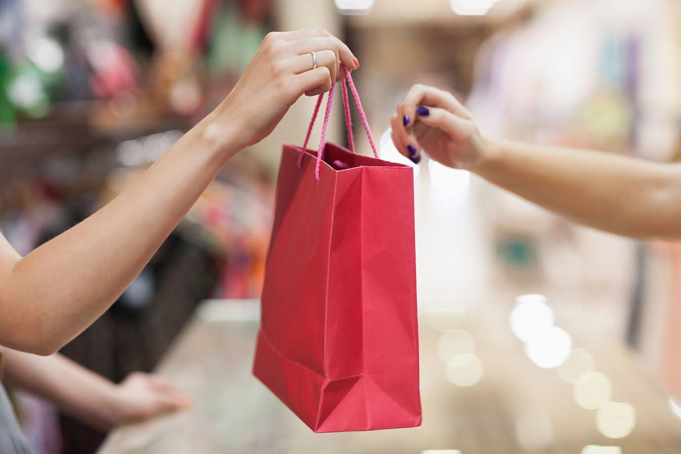 Mulher entrega sacola de compras para cliente: vendas, compras