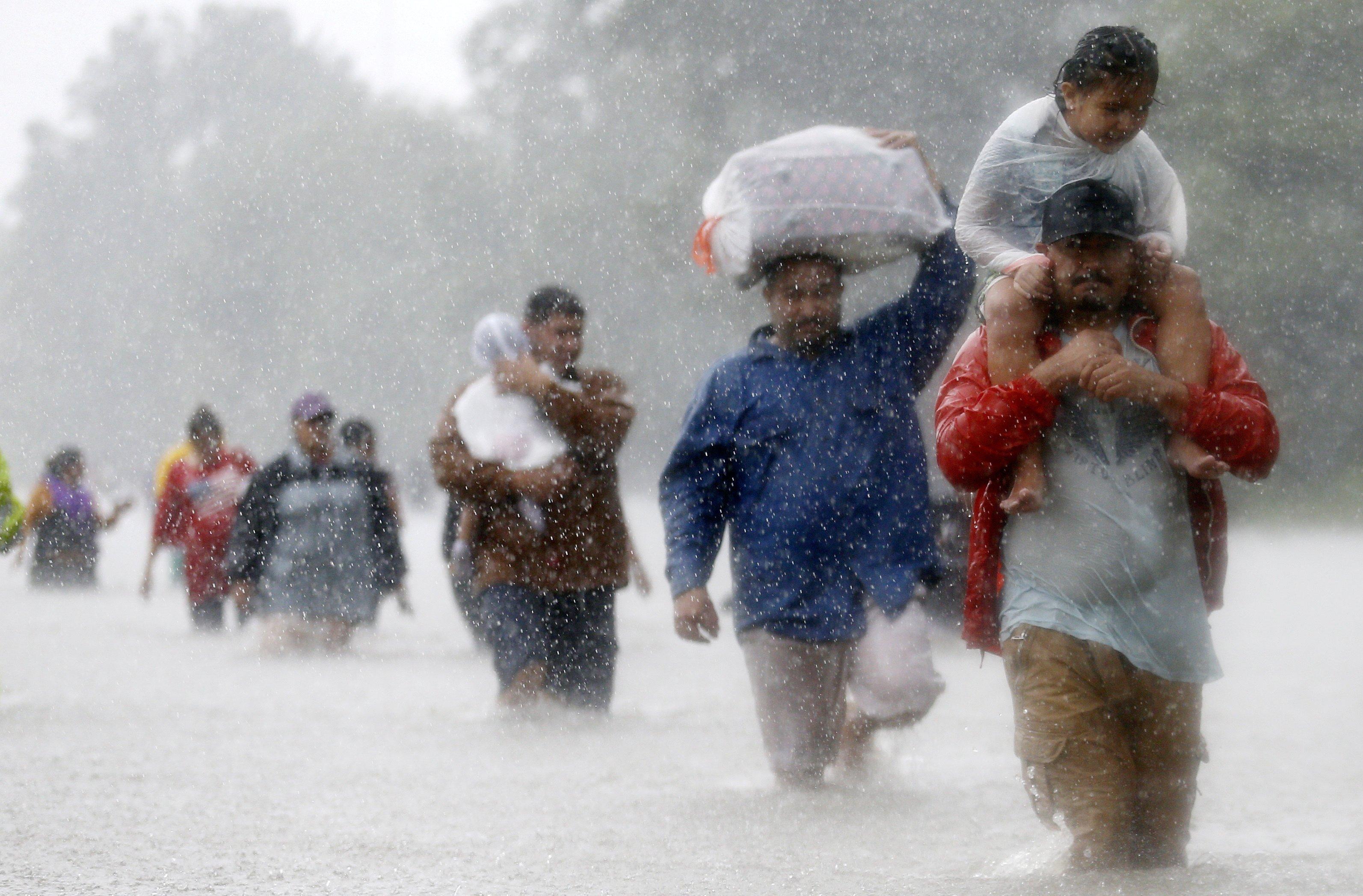 Pessoas caminham pela enchente provocada pela passagem do furacão Harvey em Houston, dia 28/08/2017