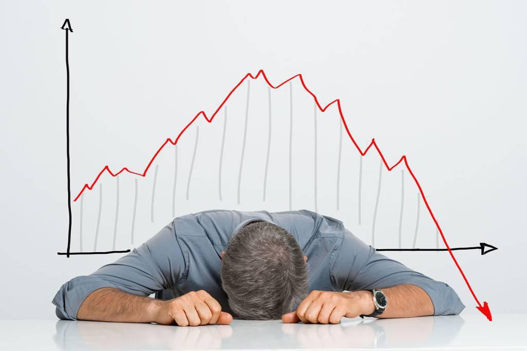 Homem com gráfico em queda: prejuízo, falência, mau investimento