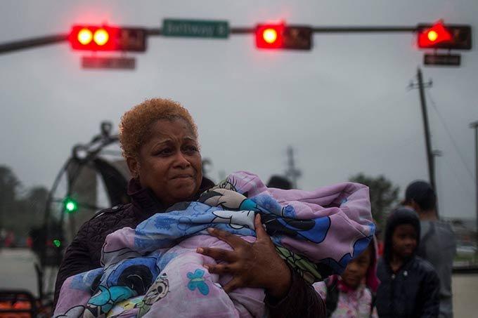 Mulher segurando criança no colo foge das enchentes em Houston provocadas pelo furacão Harvey nos Estados Unidos.