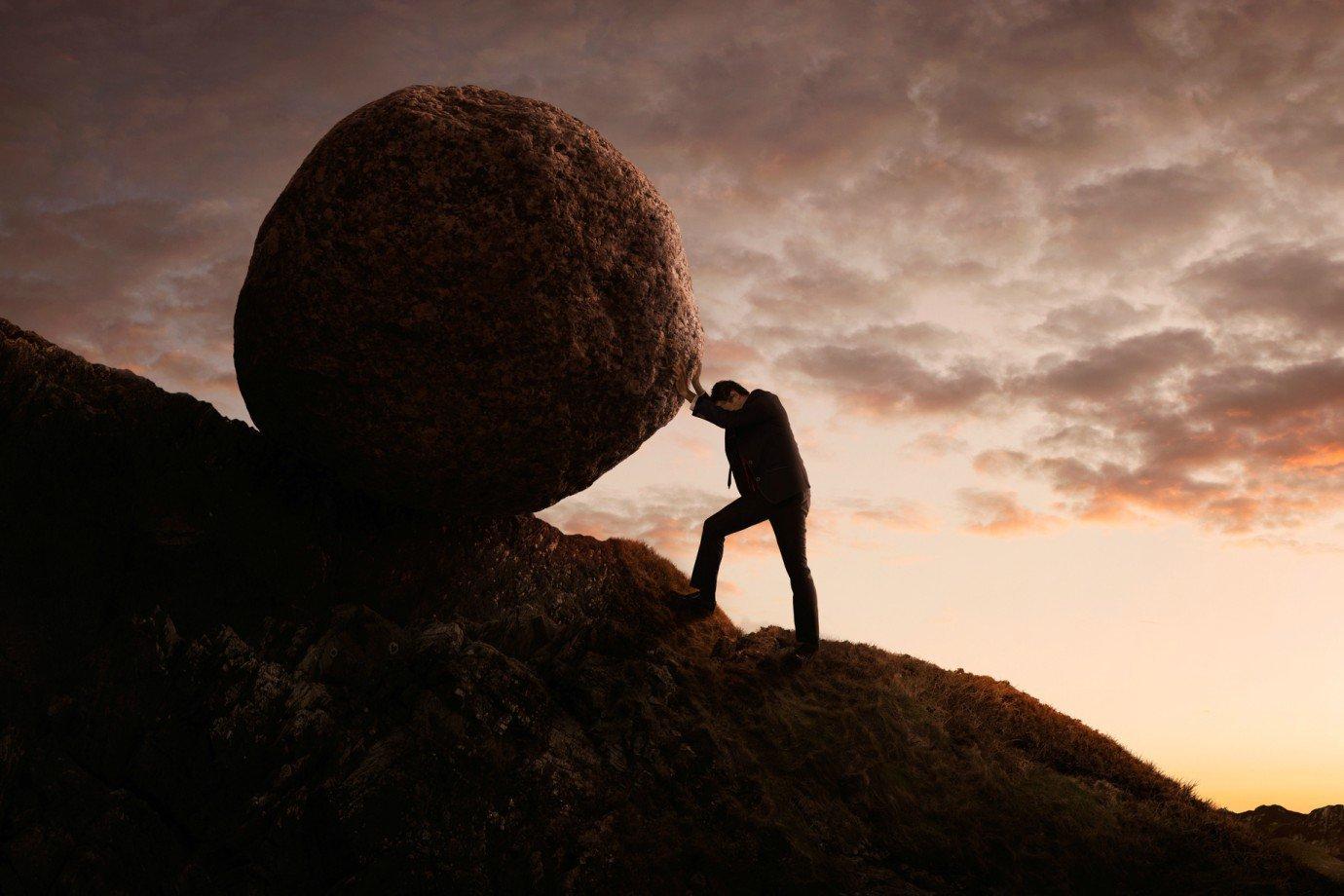 Pessoa levando pedra para o topo de uma montanha
