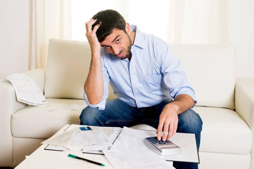 Homem preocupado com dívidas