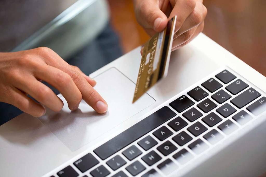 Pessoa fazendo compra em um notebook com cartão de crédito