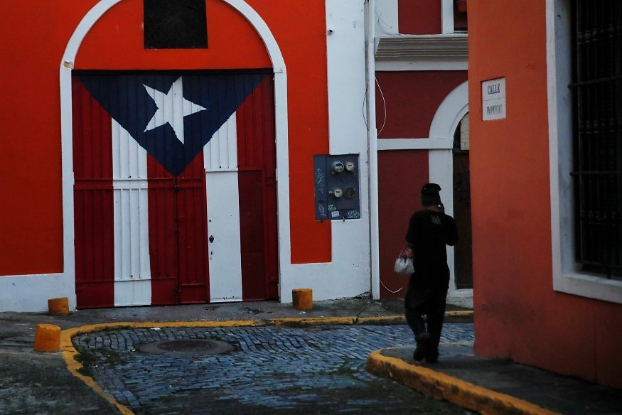 A man walks down a street in the Hurricane Maria affected area of Old San Juan