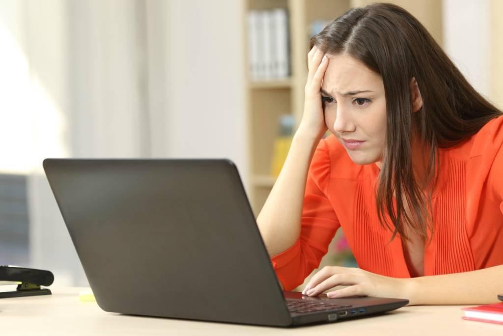 Mulher preocupada diante de laptop