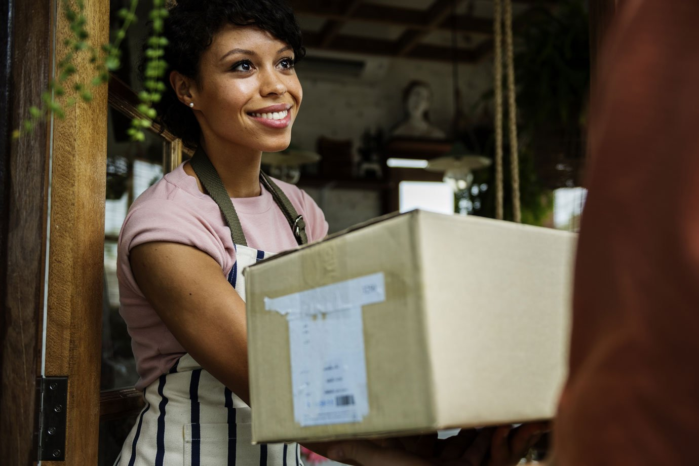 Mulher recebe caixa de entregador de delivery