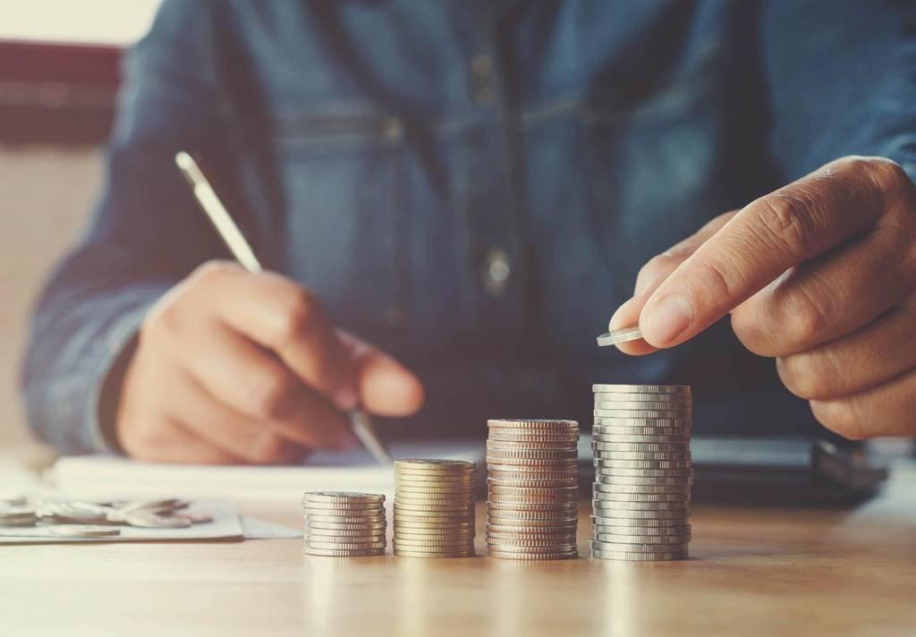Homem fazendo contas e moedas