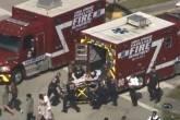 Trabalhadores de resgate se preparam para transportar uma vítima em uma maca perto de escola após tiroteio em Parkland, Flórida, EUA.