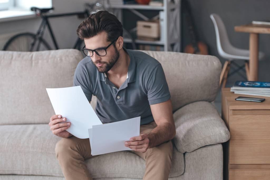 Homem analisa documentos e comprovantes