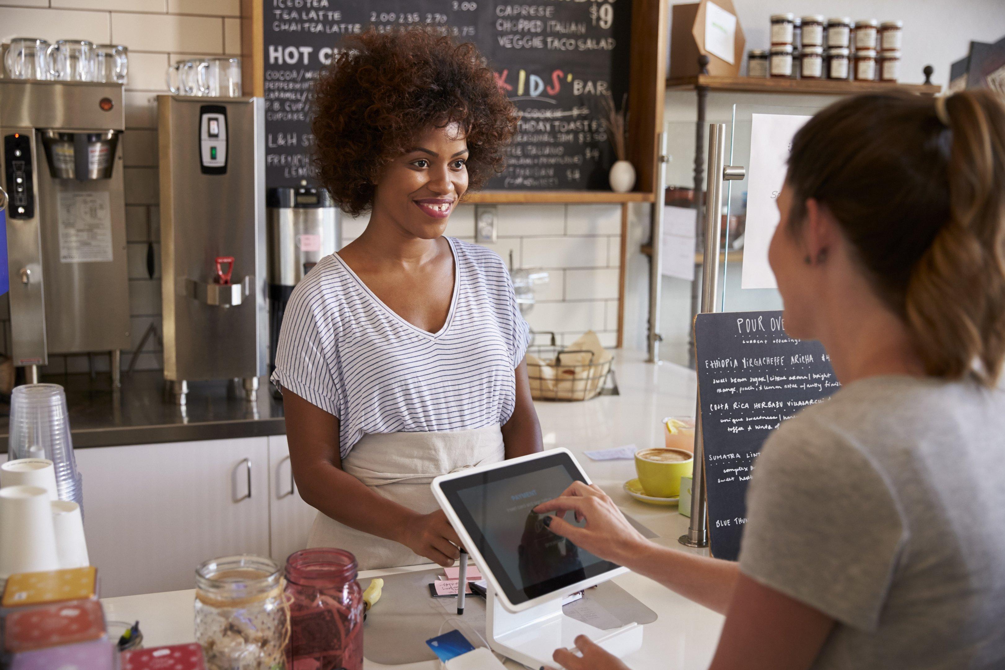 Vendedora/empreendedora e consumidor em balcão de loja, pagando