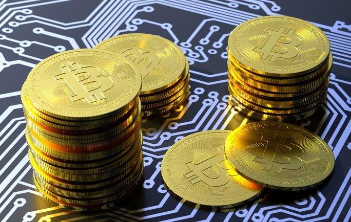 Uma pilha de moedas demarcadas com o símbolo do bitcoin sobre um circuito de computador.