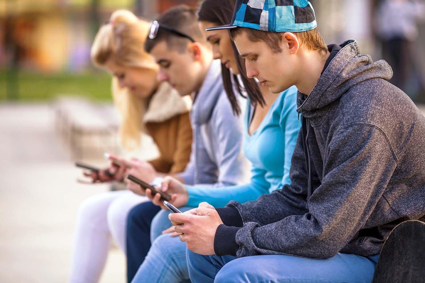 Adolescentes em local público usando seus smartphones