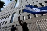 Manifestante de Honduras carrega bandeira em frente a Centro de Detenção Metropolitan