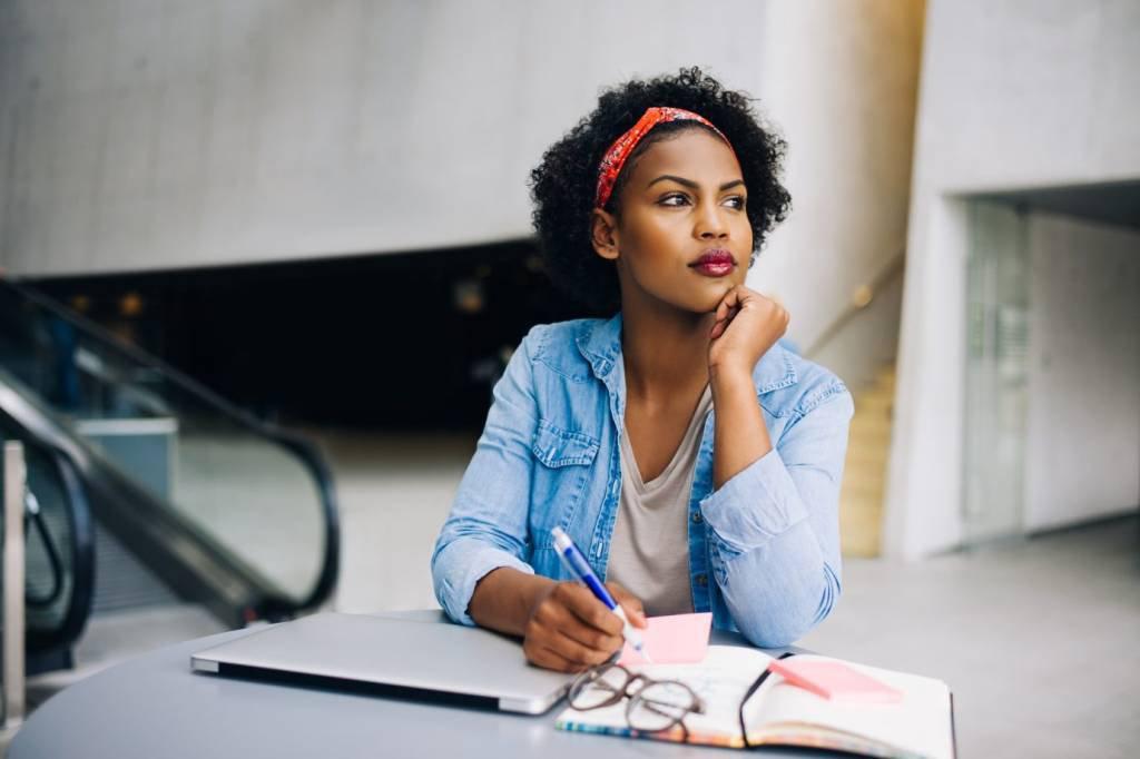 Mulher empreendedora pensa, com caderno