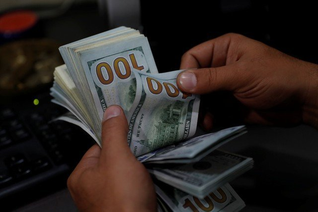 A money changer counts U.S. dollar banknotes at a currency exchange office in Izmir