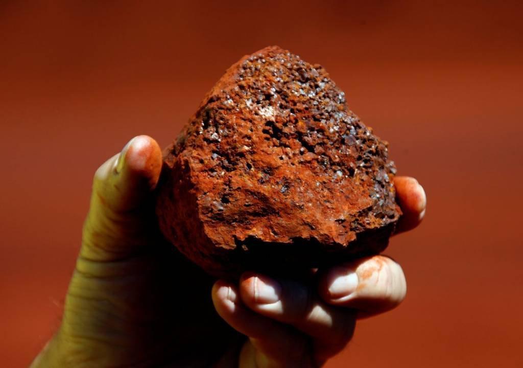 Um mineiro segura um pedaço de minério de ferro em uma mina localizada na região de Pilbara, na Austrália Ocidental