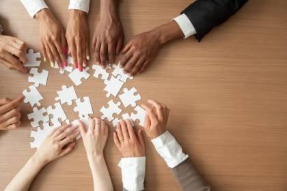 Equipe monta quebra-cabeça; trabalho em equipe, cooperação