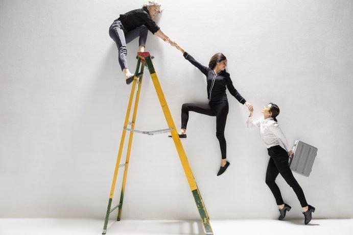 Mulheres se ajudam a subir escada, subir na carreira