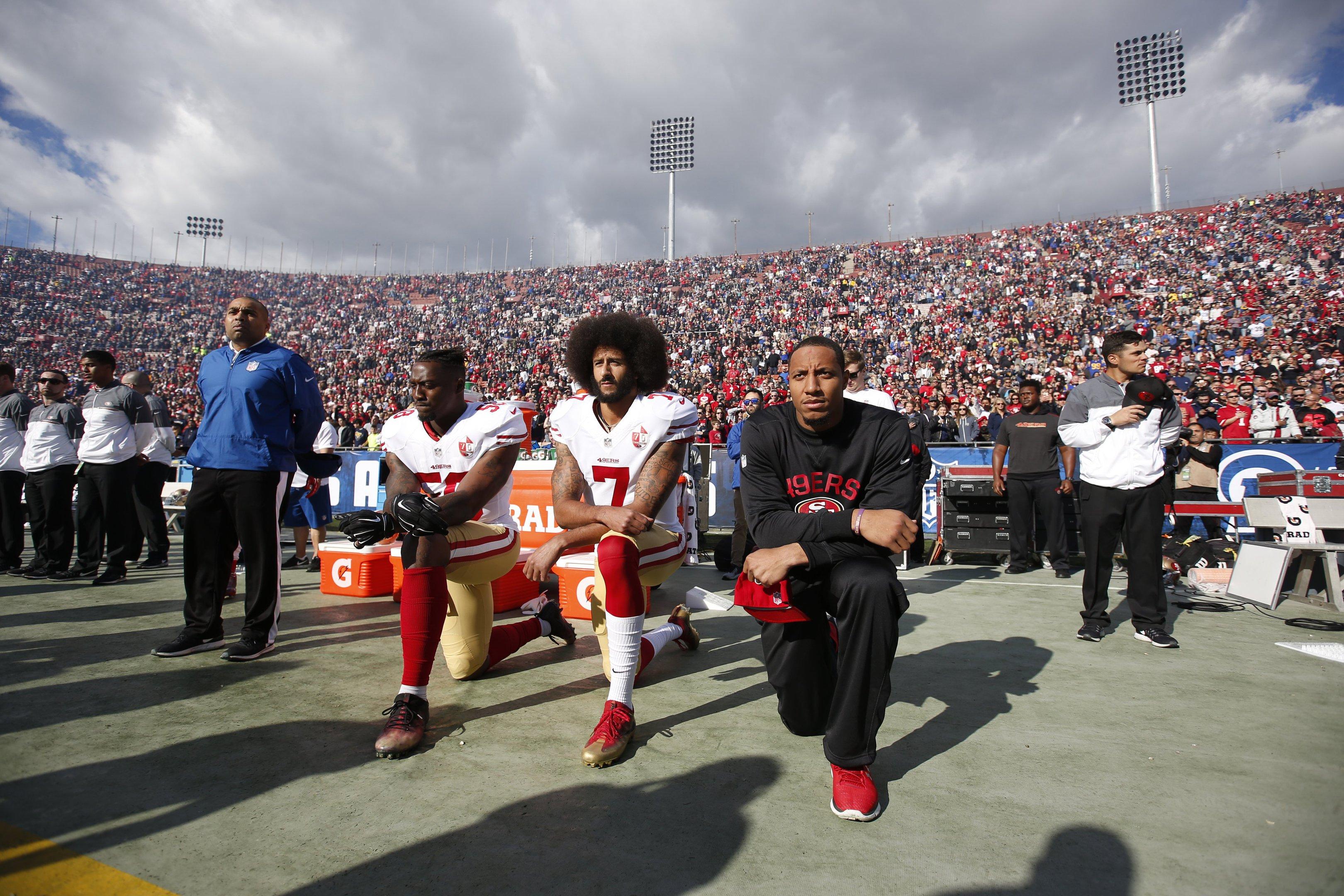 Eli Harold, Colin Kaepernick e Eric Reid do San Francisco 49ers ajoelham-se durante o hino nacional americano