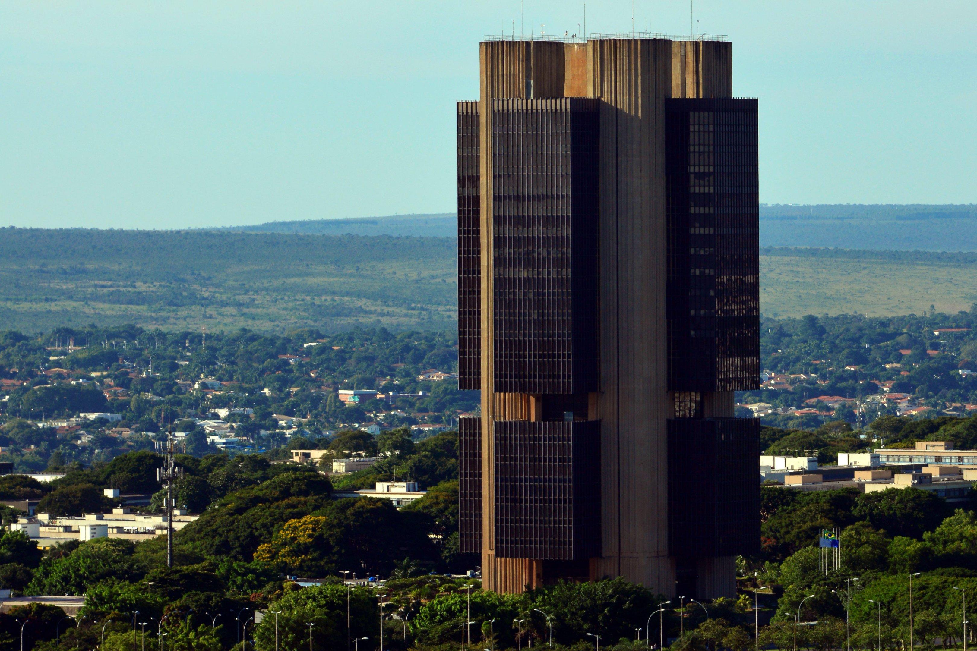 A imagem mostra a sede do Banco Central com Brasília ao fundo.