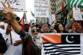 As pessoas entoam slogans enquanto seguram a representação das bandeiras da Caxemira durante uma manifestação em solidariedade ao povo da Caxemira, em Karachi, Paquistão, 6 de agosto de 2019.
