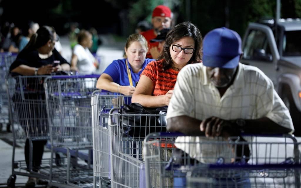 Pessoas aguardam em fila de supermercado para comprar suprimentos