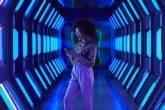Jovem profissional usa o celular em corredor futurista