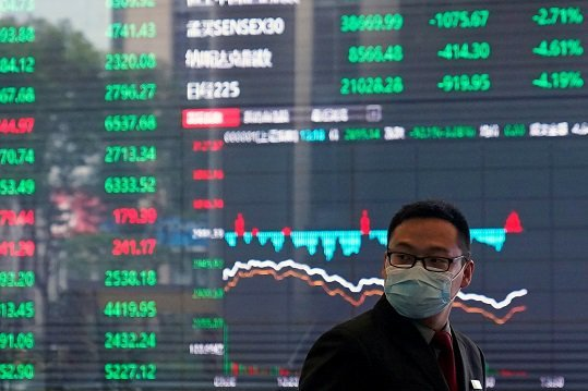A man wearing a protective mask is seen inside the Shanghai Stock Exchange building, as the country is hit by a new coronavirus outbreak, at the Pudong financial district in Shanghai
