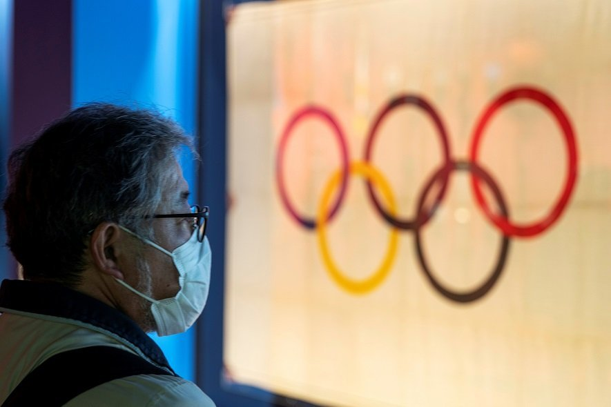 A man wearing a protective face mask, following an outbreak of the coronavirus, stands in front of The Tokyo Olympic flag 1964 at The Japan Olympics museum in Tokyo