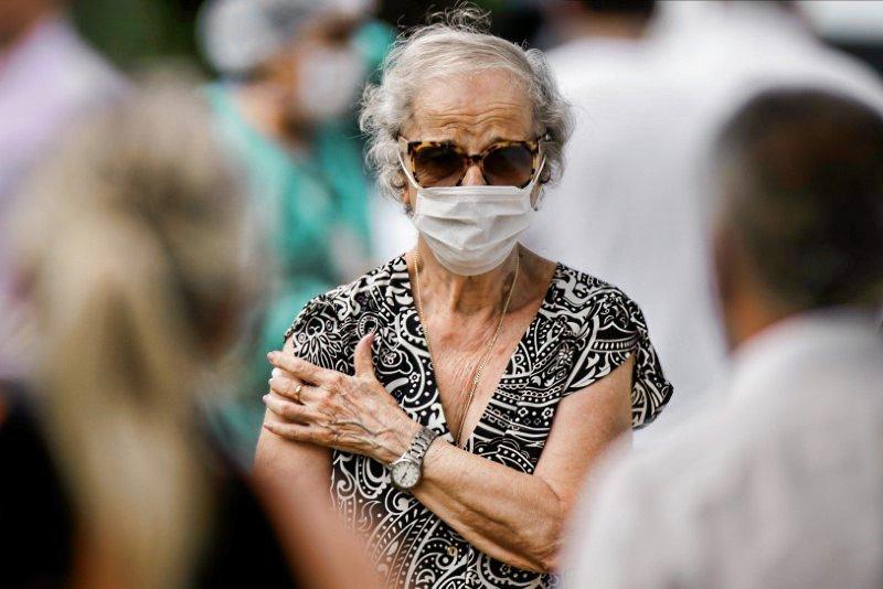 Mulher caminha após receber vacina da gripe em Brasília, em meio a surto da doença do coronavírus (Covid-19)