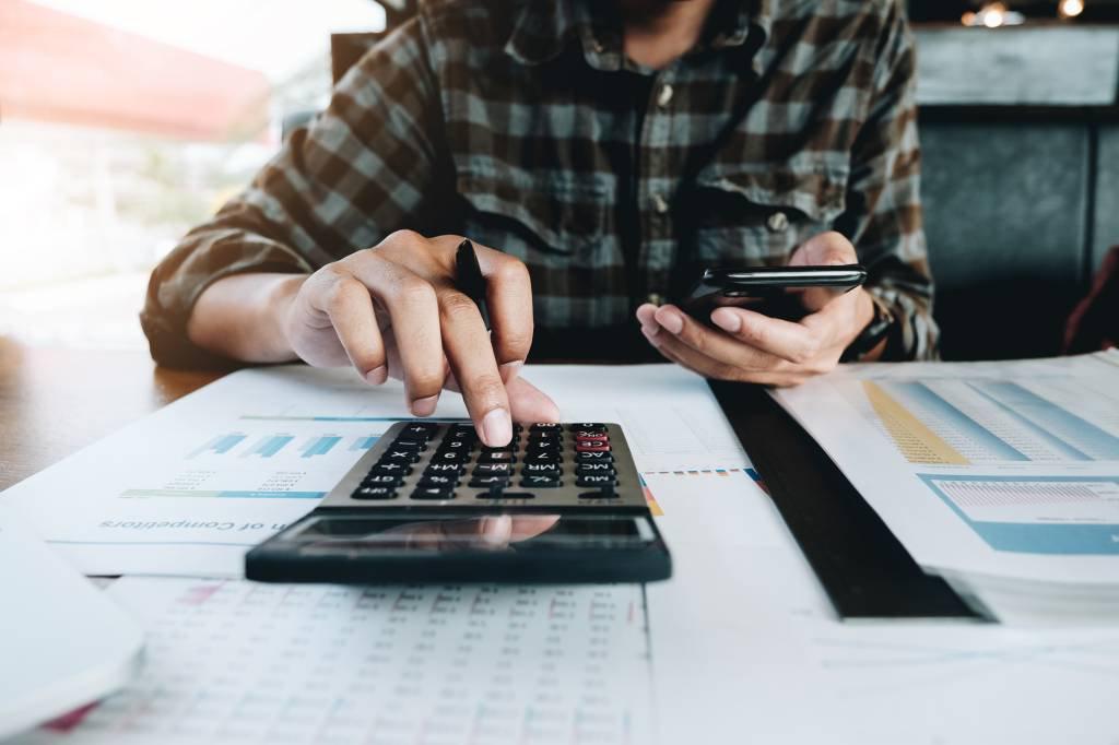 Homem fazendo contas na calculadora