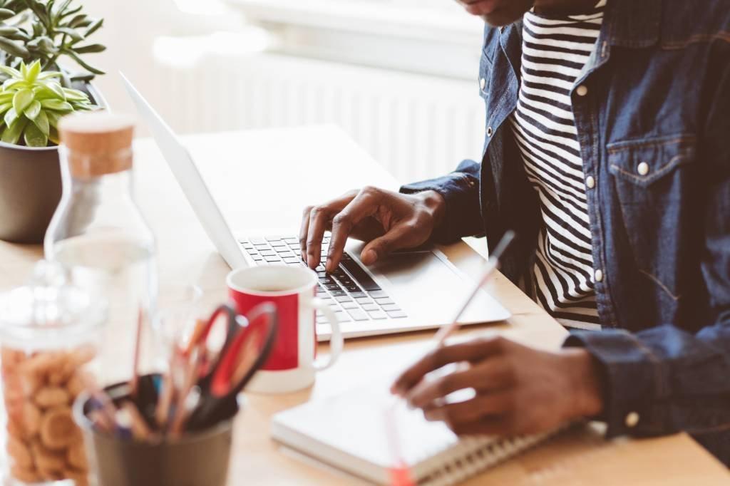 Pessoa escrevendo e usando computador