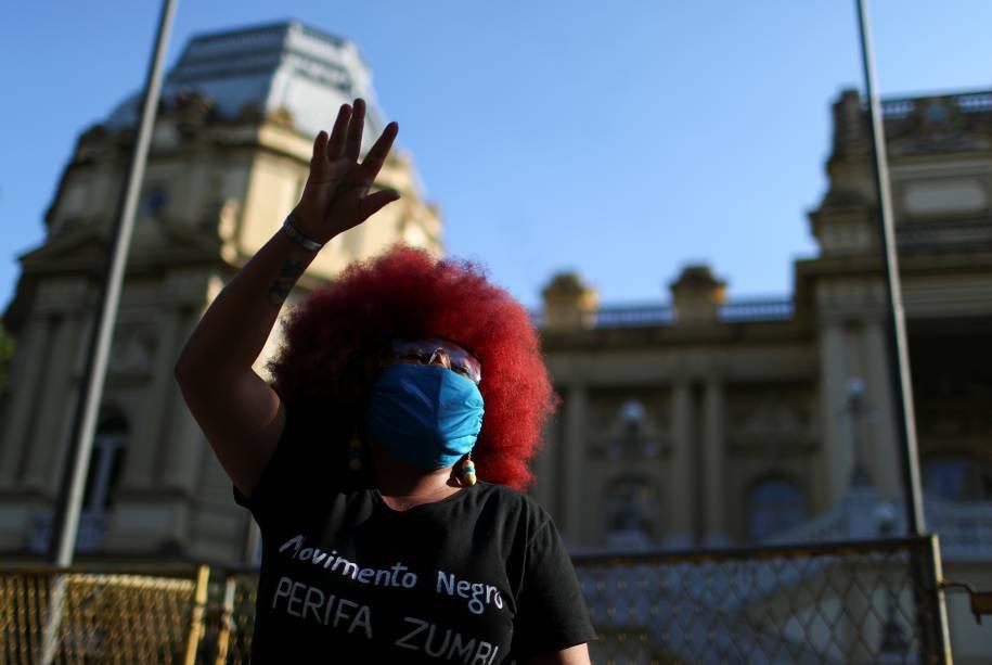 Mulher usa máscara protetora em protesto contra a violência policial durante operações em favelas contra gangues de drogas e racismo no Brasil, em frente ao Palácio da Guanabara, no Rio de Janeiro, Brasil, 31 de maio de 2020.