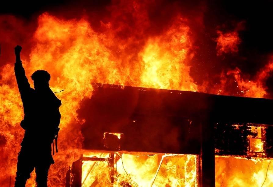 Manifestante em frente a escombros em chamas durante ato em Minneapolis, onde um policial matou George Floyd. 30 de maio