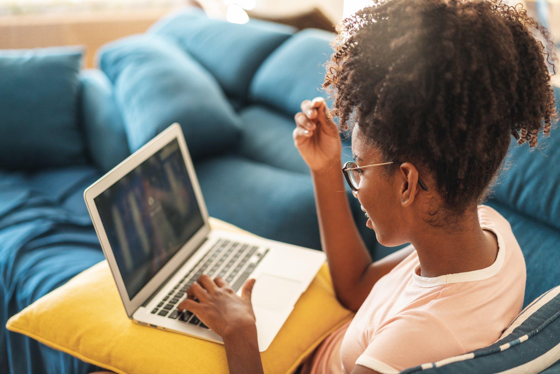 Donna di colore che utilizza computer sul divano di casa.