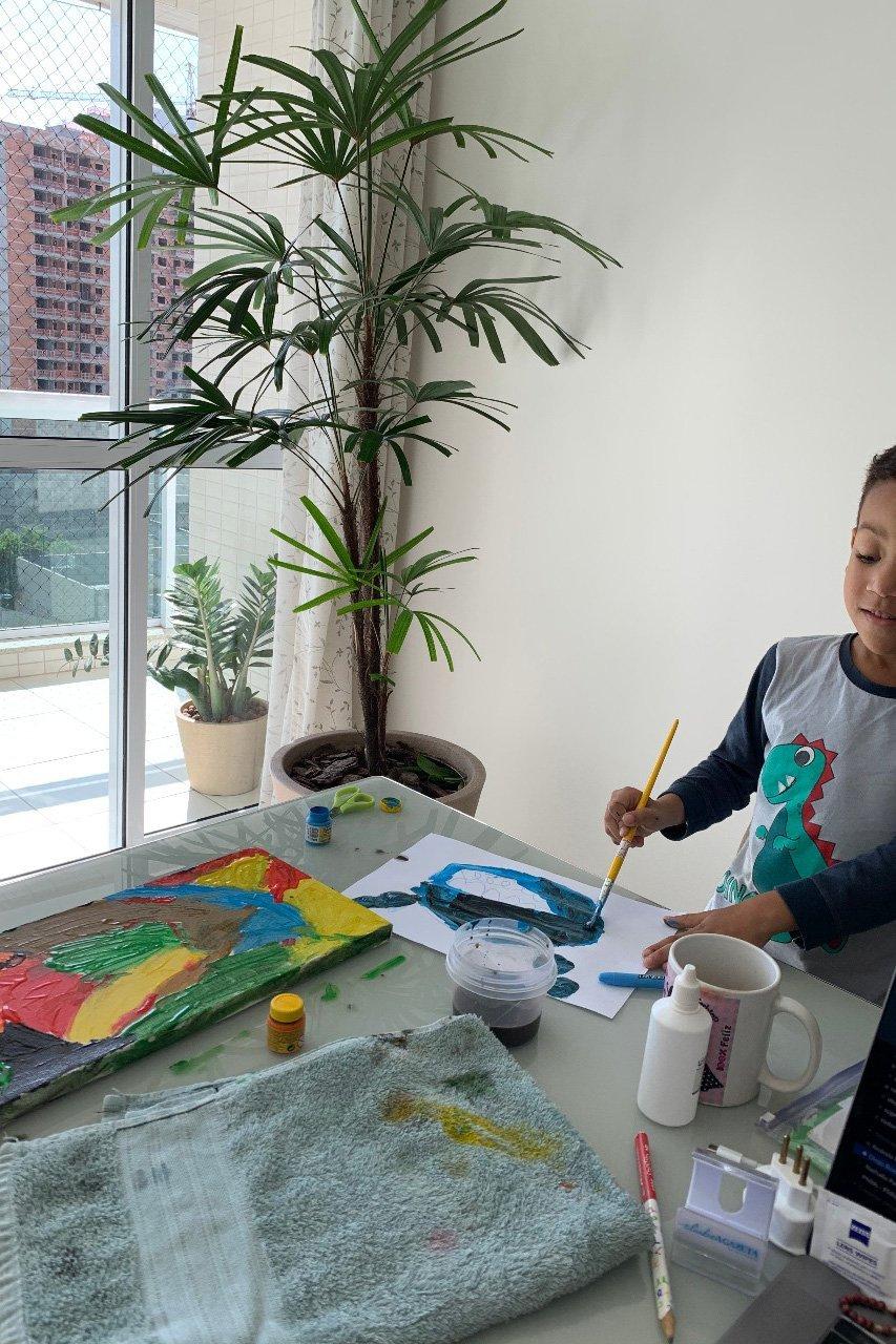 Heitor, de 5 anos, é filho da Rubia Cardoso, gerente de Operações da PicPay, e está fazendo uma arte na mesa enquanto sua mãe trabalhar
