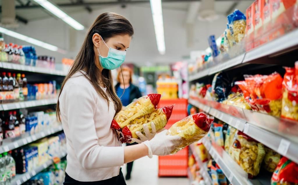 Mulher fazendo compras em supermercado na pandemia