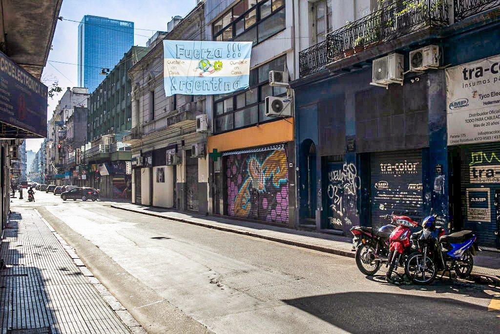 """Bandeira argentina com a frase: """"força, Argentina"""" em rua com comércio fechado em Buenos Aires. 20 de junho de 2020."""