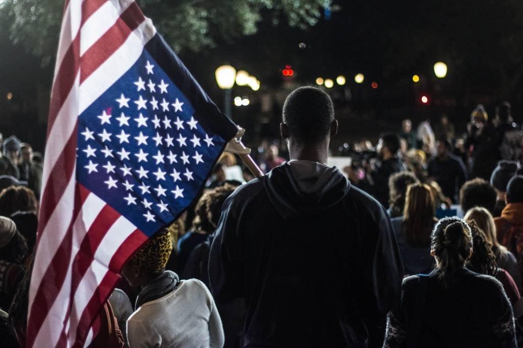 Americano negro segura bandeira dos Estados Unidos durante protesto contra a violência policial e o racismo