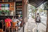 Pedestre usando máscara protetora passa por pessoas sentadas em um restaurante no bairro Vila Madalena, em São Paulo. Segunda-feira, 6 de julho de 2020.