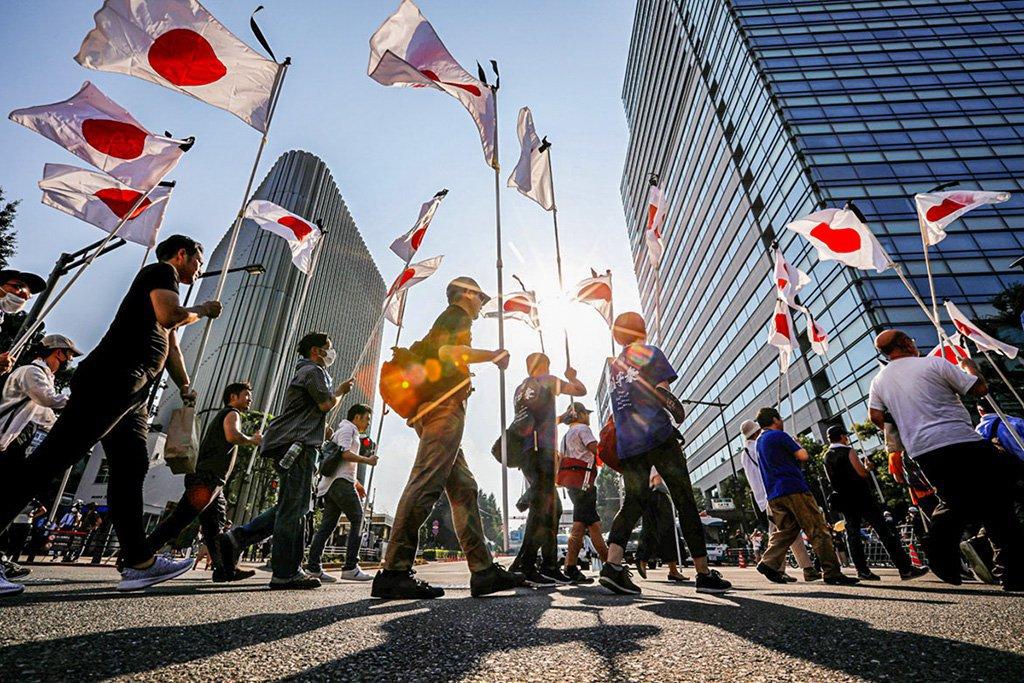 """Membros do movimento nacionalista """"Ganbare Nippon"""" segurando bandeiras nacionais japonesas marcham perto do santuário Yasukuni enquanto prestam homenagem aos mortos na guerra no 75º aniversário da rendição do Japão na Segunda Guerra Mundial, em meio ao surto da doença coronavírus (COVID-19), em Tóquio , Japão, 15 de agosto de 2020. REUTERS / Issei Kato"""