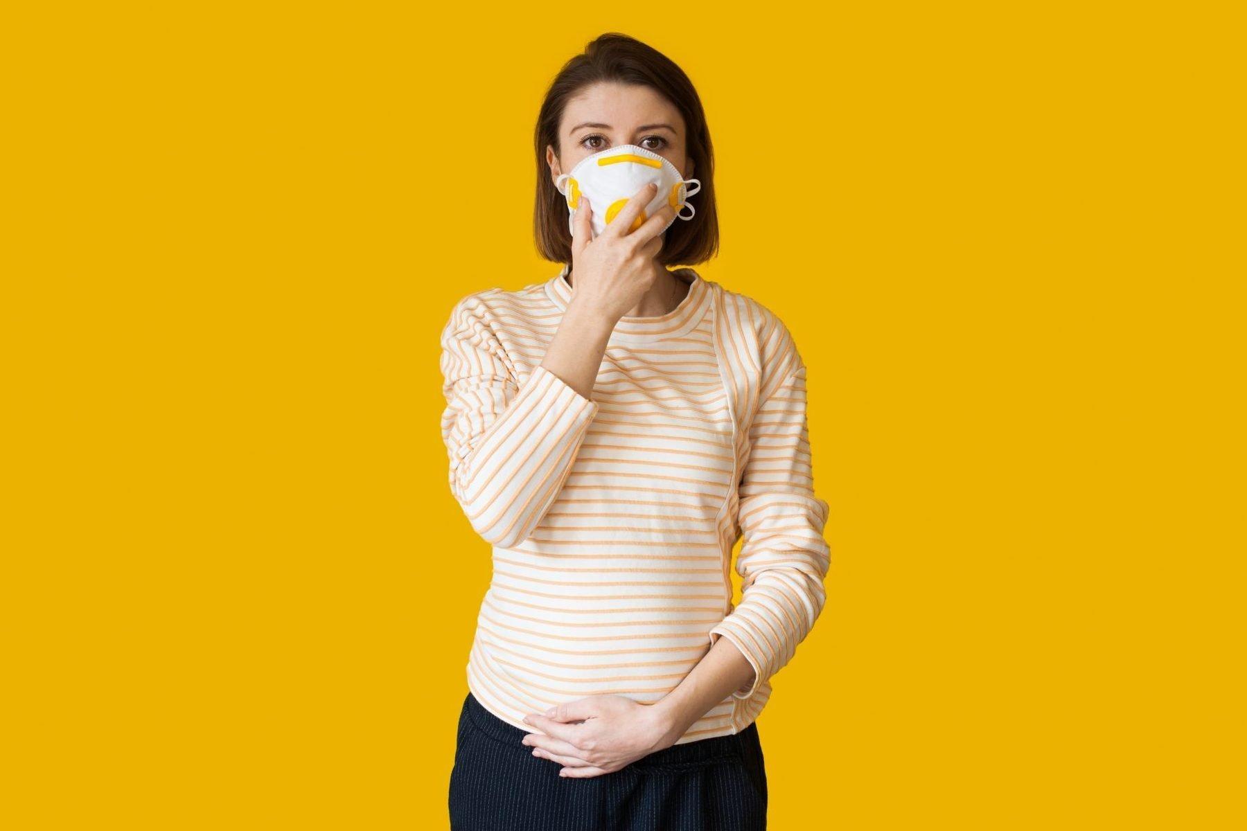 Mulher grávida com máscara no rosto