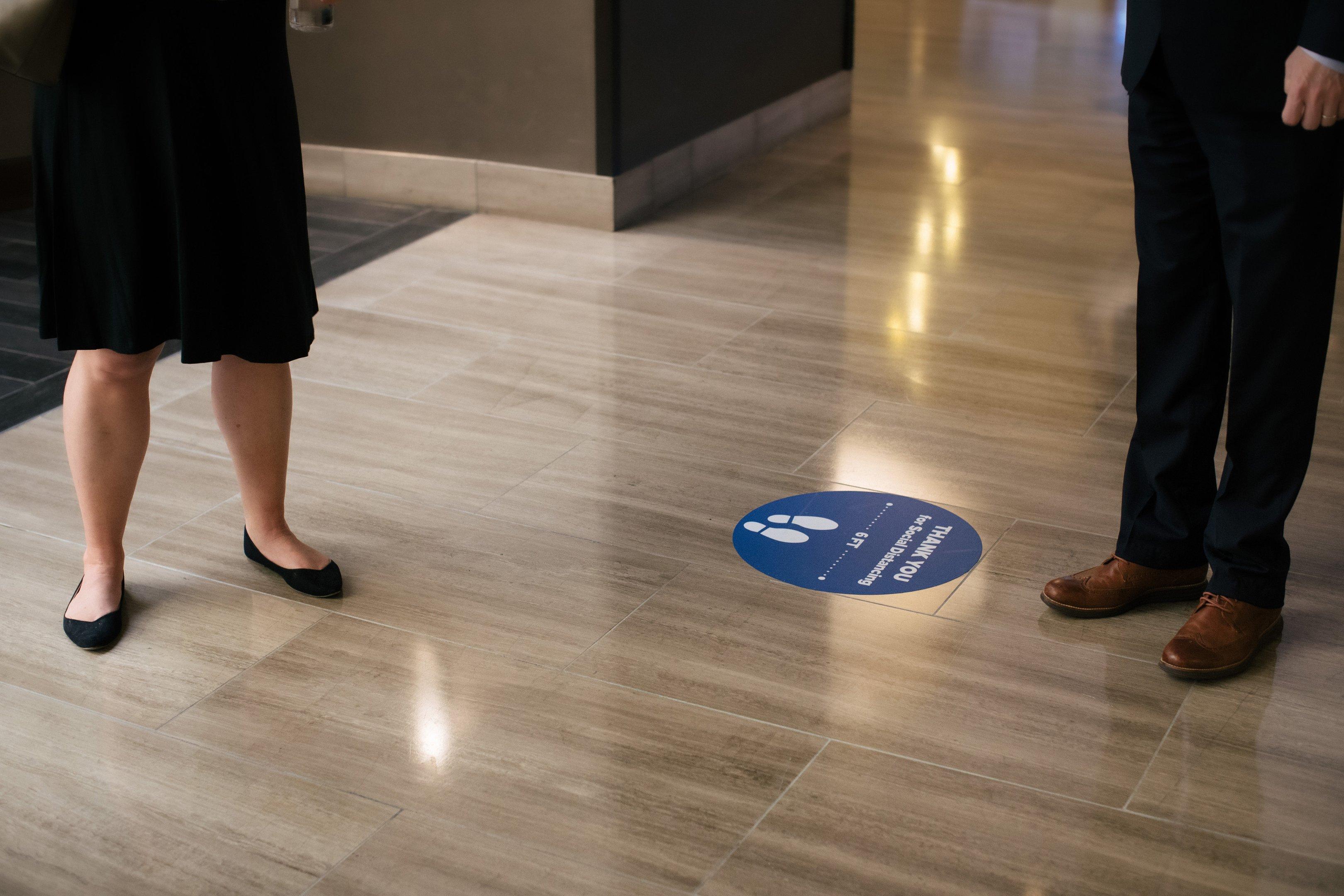 No chão do Hilton McLean Tysons Corner, lembrete para distância social