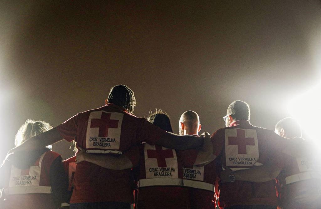 Membros da Cruz Vermelha se abraçam como um colete de voluntário da Cruz Vermelha é projetado na estátua do Cristo Redentor para homenagear sua assistência aos brasileiros durante o surto da doença coronavírus (COVID-19), no Rio de Janeiro, Brasil, 31 de agosto de 2020 . REUTERS / Ricardo Moraes